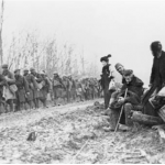 French refugees watch the regiment march through the Bois de Boliers near Sedan 9 November 1918 - the day after the death of Private Patterson.